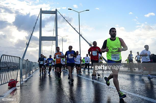 Participants run on the July 15 Martyrs' Bridge known as the Bosphorus Bridge during the 38th annual Istanbul Marathon on November 13 2016 / AFP /...