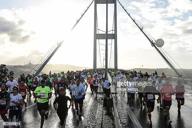 TOPSHOT Participants run on the July 15 Martyrs' Bridge known as the Bosphorus Bridge during the 38th annual Istanbul Marathon on November 13 2016 /...