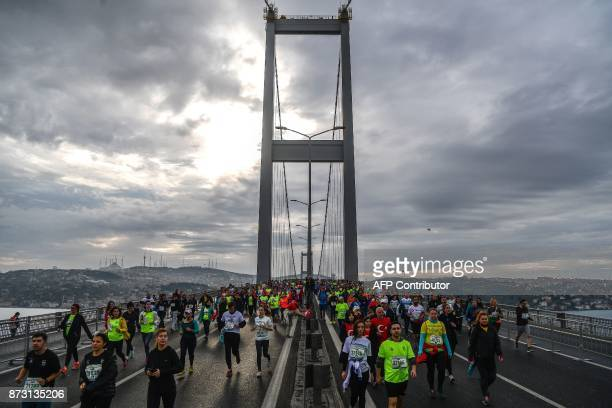 TOPSHOT Participants run on the July 15 Martyrs' Bridge known as the Bosphorus Bridge during the 39th annual Istanbul Marathon on November 12 in...