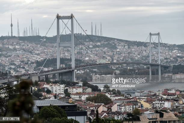 Participants run on the July 15 Martyrs' Bridge known as the Bosphorus Bridge during the 39th annual Istanbul Marathon on November 12 in Istanbul /...