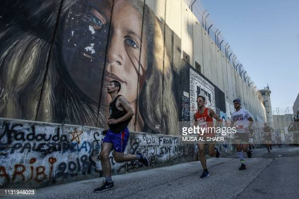 Participants run past a mural depicting the Palestinian activist Ahed Tamimi drawn along Israel's controversial separation barrier which divides the...