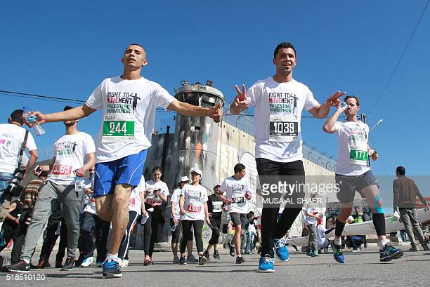 Participants run past a section of Israel's separation barrier near the biblical West Bank town of Bethlehem during the 4th Palestine Marathon on...