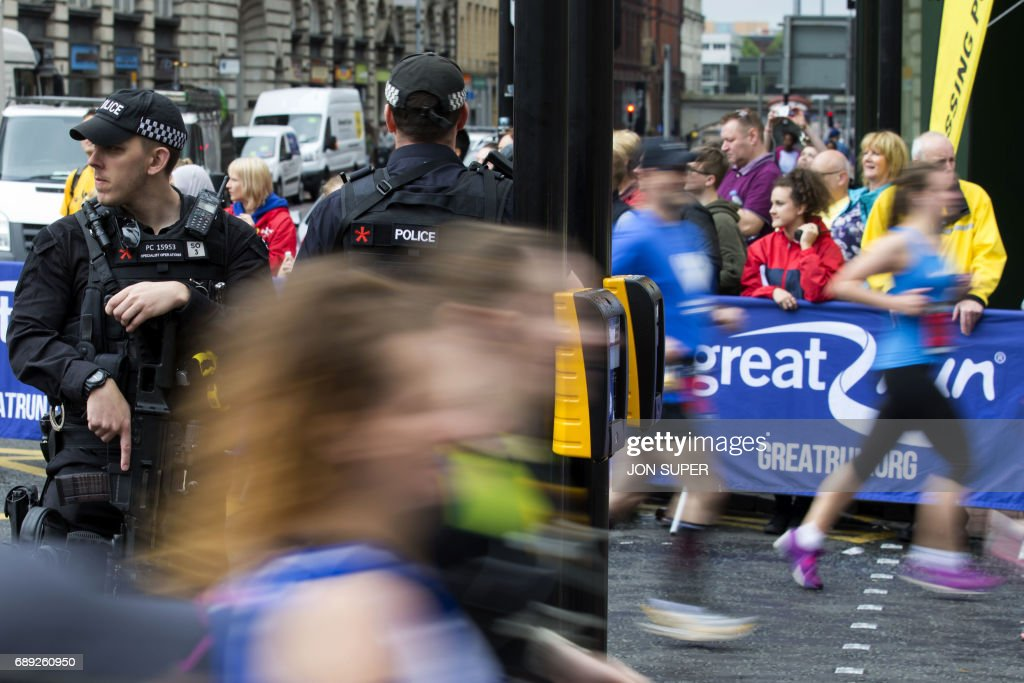 Participants run past armed police at the start of the Great Manchester Run in Manchester on May 28, 2017. Britain police have released CCTV footage of Manchester bomber Salman Abedi on the night of the attack as thousands defied the terror threat to take part in the Great Manchester Run on Sunday. /