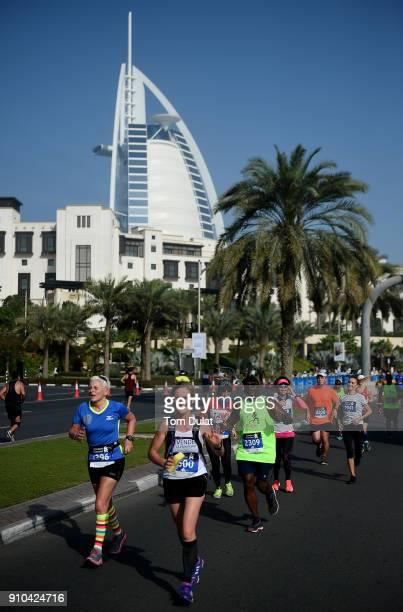 Participants run past Burj Al Arab during the Standard Chartered Dubai Marathon on January 26 2018 in Dubai United Arab Emirates