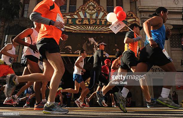 Participants run past the El Capitan theatre along Hollywood Blvd during the LA Marathon Sunday