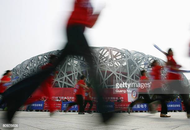 Participants run past the National Stadium, also known as the 'Bird's Nest' on April 30, 2008 in Beijing, China. Chinese authorities have organized...
