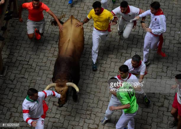 Participants run with a Puerto de San Lorenzo's fighting bull during the third bull run of the San Fermin festival in Pamplona northern Spain on July...