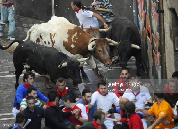Participants run with Dolores Aguirre Ybarra fighting bulls on the fifth release of bulls during the San Fermin bull run on July 11 in Pamplona...