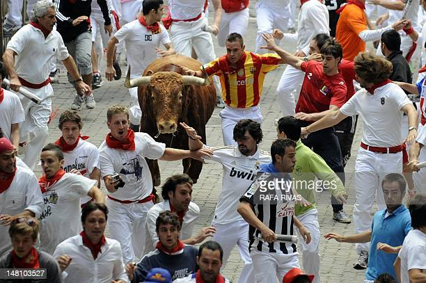 Participants run with El Pilar bulls during the fourth bull run of the San Fermin Festival on July 10 in the Northern Spanish city of Pamplona AFP...