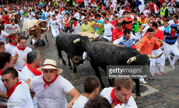 Participants run with fighting bulls during the San Fermin running of the bulls on July 10 2011 in Pamplona Spain For eight days fighting bulls run...