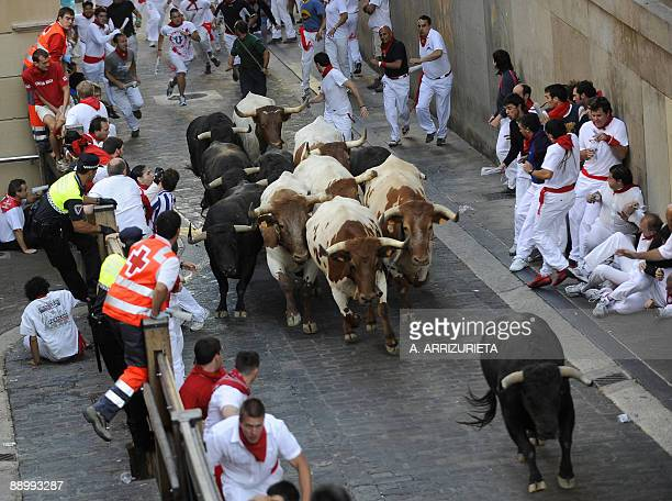 Participants run with Fuente Ymbro fighting bulls on the seventh day of the San Fermin Festival bull run on July 13 in Pamplona northern Spain The...