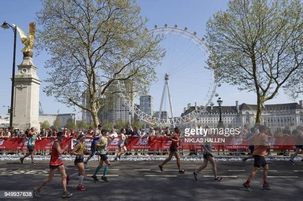 Participants run with the London Eye in the background at the 2018 London Marathon in central London on April 22 2018