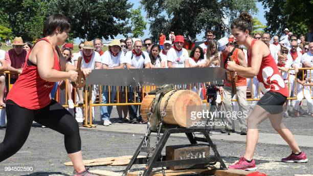 Participants saw a tree trunk with a 'tronza' a traditional Basque saw during a rural Basque sports championship on the third day of the San Fermin...