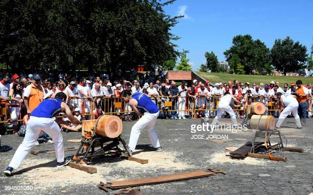 Participants saw tree trunks with 'tronzas' traditional Basque saws during a rural Basque sports championship on the third day of the San Fermin bull...