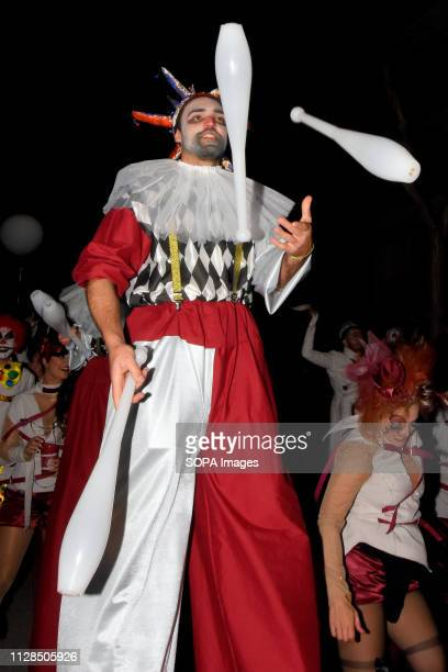 A participants seen dressed up in a colourful costume juggling during the carnival According to tradition people dress up in different colorful...