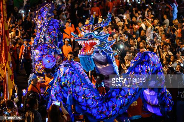 Participants seen performing with a replica of a dragon during the Cap Go Meh festival Cap Go Meh festival in downtown Singkawang involves rituals of...
