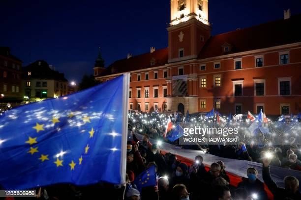 Participants show the light of their mobile phones and wave EU flags over a large Polish flag as they take part in a pro-EU demonstration following a...