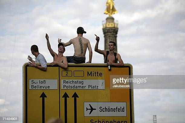 Participants sit at a traffic sign at the 16th annual Loveparade weekend July 15 2006 in Berlin Germany Over 300 DJs on 39 trucks so called floats...