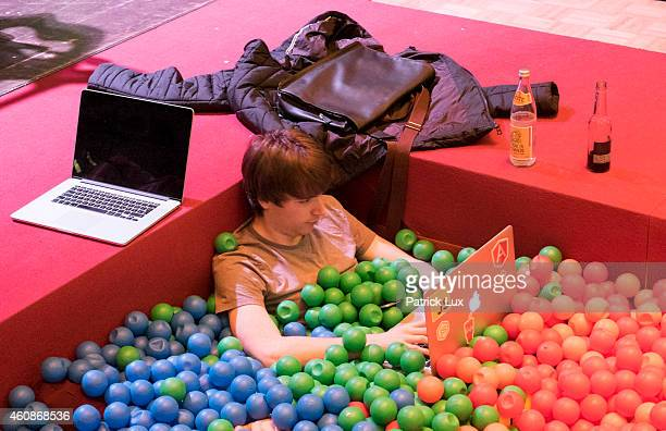 A participants sits with his laptop computer in a ball bath at the 31st annual Chaos Communication Congress on December 28 2014 in Hamburg Germany...