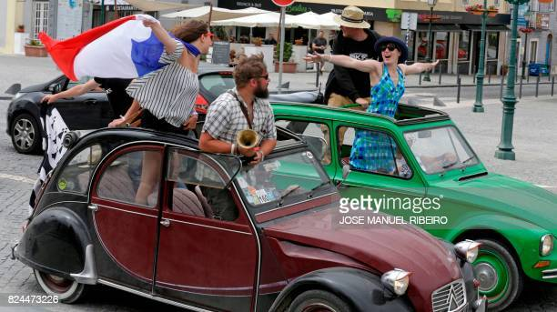 Participants stand in their vehicles during the parade of Citroen classic cars 2CV in Mafra during the World 2017 2CV Meeting July 30, 2017. - The...