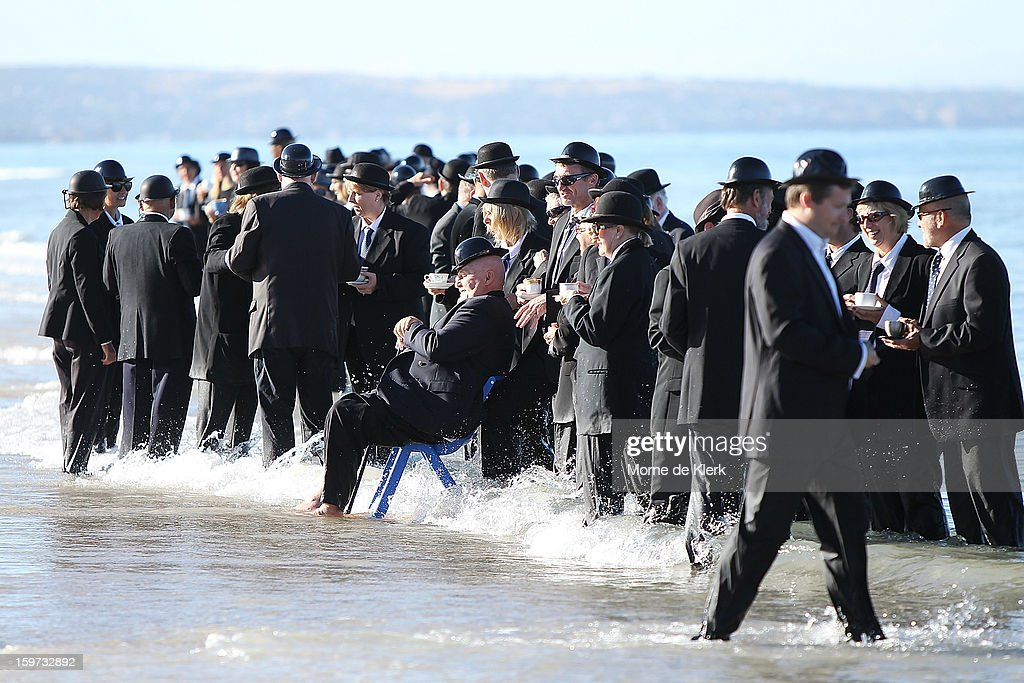 Participants stand on the beach dressed in suits and bowler hats as part of an art installation created by surrealist artist Andrew Baines on January 20, 2013 in Adelaide, Australia.