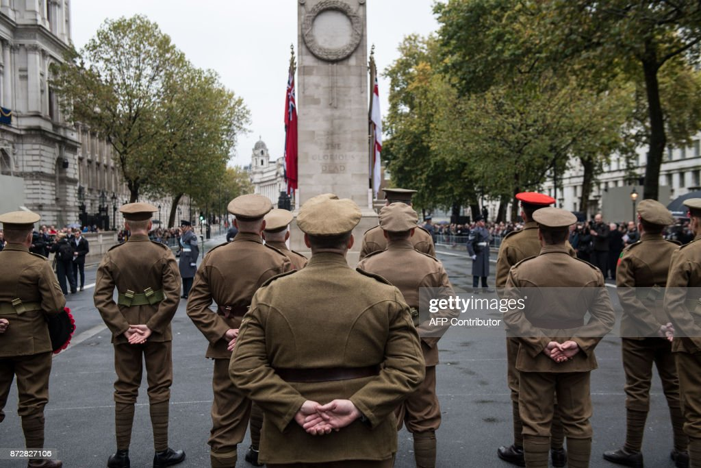 Participants stand to attention during the Western Front Association's (WFA) annual service of remembrance on Armistice Day, at the Cenotaph in central London on November 11, 2017. /
