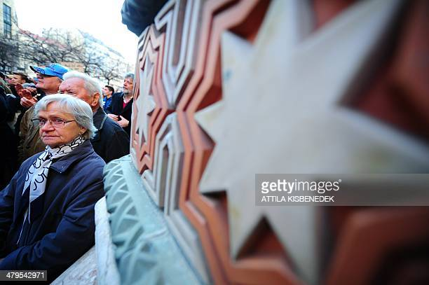 Participants stand to commemorate in front of the local synagogue of Budapest on March 19 2014 during a commemoration of the victims of Nazis...
