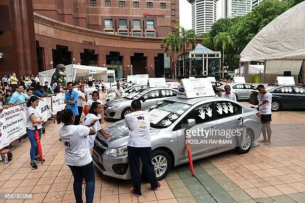 Participants stand with their hand placed on a car during day 4 of the Subaru Challenge at the Ngee Ann City Plaza in Singapore on November 11 2014...