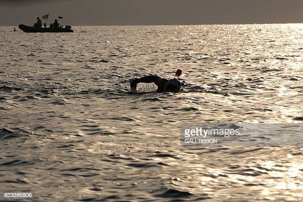 Participants take part in a 17kilometre swim from Jordan to Israel across the Dead Sea organised by the EcoPeace charity aimed at raising awareness...