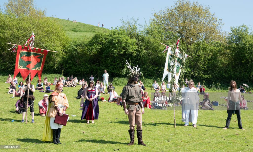 Participants take part in a ceremony below Glastonbury Tor as they take part in May Fayre and Dragon Procession in Glastonbury on May 6, 2018 in Somerset, England. To celebrate the arrival of summer, the Glastonbury Dragons, alongside Gwythyr Ap Greidal, the Summer King and the Winter King, Gwyn Ap Nudd, were paraded through the town to the lower slopes of Glastonbury Tor where the event was marked with a Beltane themed ceremony.