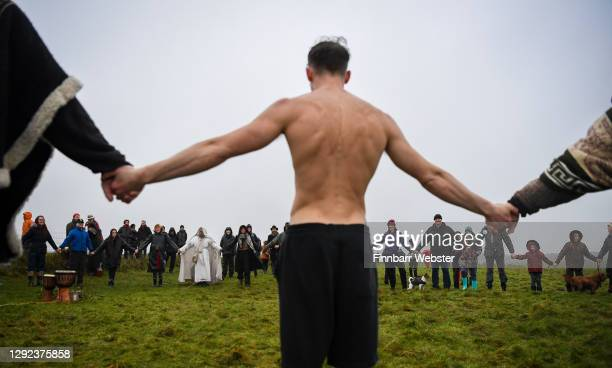 Participants take part in a ceremony for the Winter Solstice at the closed Stonehenge on December 21, 2020 in Amesbury, United Kingdom. English...