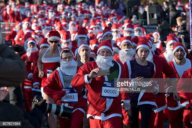 Participants take part in a charity 'Santa Dash' 5k and 10k runs around Clapham Common in south London on December 4 2016 / AFP / Justin TALLIS