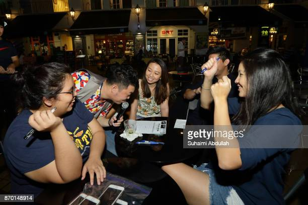 Participants take part in a mass pub quizstyle trivia game at the Trivia Zone during the Singapore River Festival 2017 at Robertson Walk on November...
