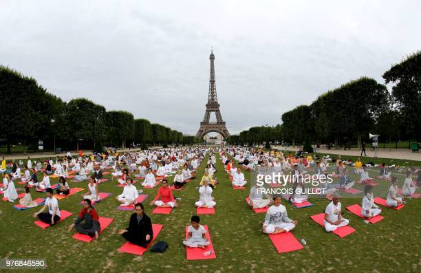 TOPSHOT Participants take part in a mass yoga event on the Champs de Mars in front of the Eiffel tower in Paris on June 17 2018 in celebration of the...