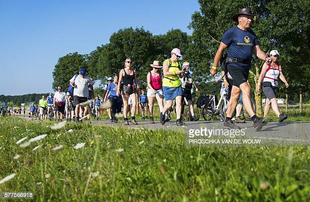 Participants take part in the 100th edition of the annual Four Days March of Nijmegen the Netherlands on July 19 2016 The 'Nijmeegse Vierdaagse' is...