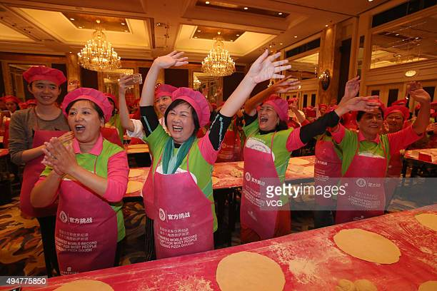 Participants take part in tossing pizza dough as they officially break the Guinness World Record for the most people tossing pizza dough at Shanghai...