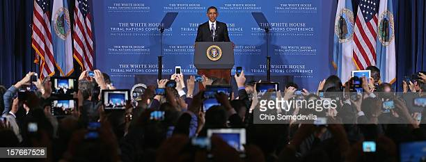 Participants take photos using their phones and tablet computers as US President Barack Obama delivers remarks during the closing session of the...