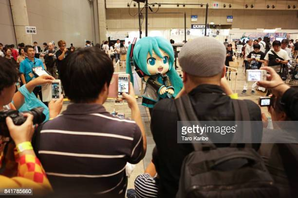 Participants take pictures of a costume of Hatsune Miku on September 1 2017 in Chiba Japan Hatsune Miku singing voice synthesizer developed by music...