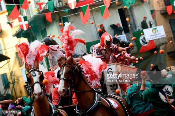 TOPSHOT Participants throw oranges from a float during the traditional Oranges battle of Ivrea Carnival near Turin on February 11 2018 Established in...