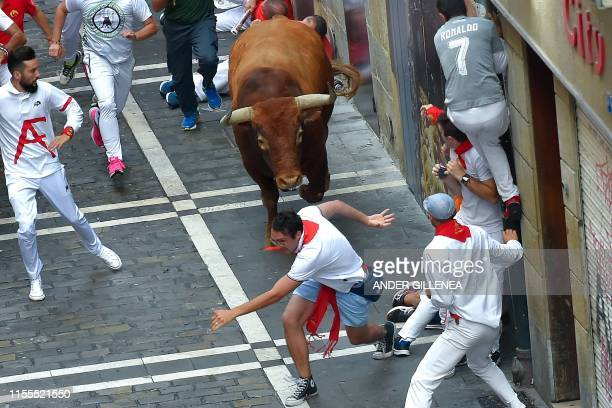 Participants try to avoid a Miura fighting bull on the last bullrun of the San Fermin festival in Pamplona northern Spain on July 12 2019 People from...
