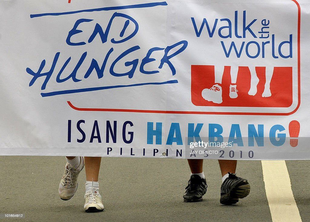 Participants walk as part of the 'Walk the World' campaign in Manila June 6, 2010, an education and fund-raising effort bringing hundreds of thousands of people to walk during 24 time zones in 24 hours. The campaign is intended to raise funds for the UN World Food Programme to help the 90 million hungry people in more than 70 countries. Organisers of the event estimate that more than 17,000 children die of hunger every day. AFP PHOTO/Jay DIRECTO