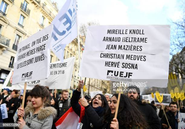 Participants walk holding placards during a silent march in Paris on March 28 in memory of Mireille Knoll an 85yearold Jewish woman murdered in her...