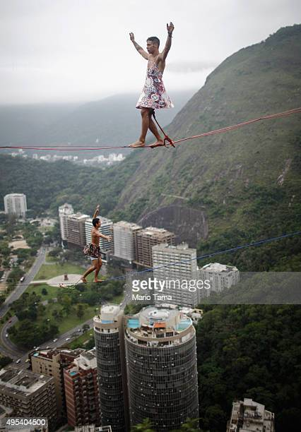 Participants walk on slacklines set up between rocks in the Cantagalo favela community during the Highgirls Brasil festival on November 2 2015 in Rio...