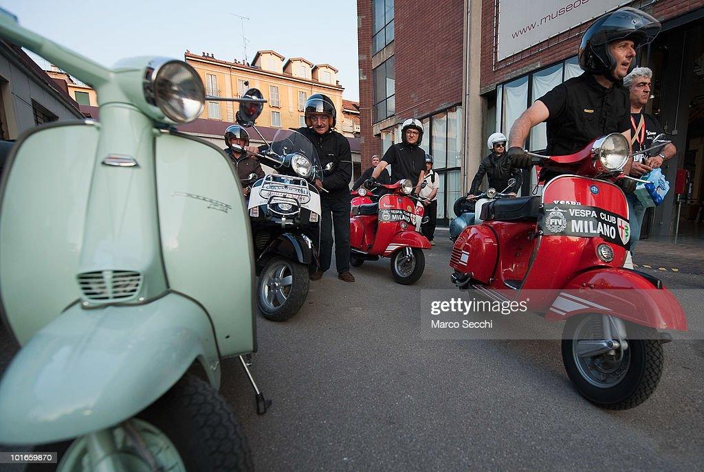 Participants walk past a Lambretta before the start of the Vespa