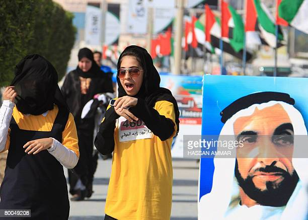 Participants walk past a portrait of late Emirati leader Sheikh Zayed bin Sultan alNahayan during the Zayed International Marathon in the Gulf...
