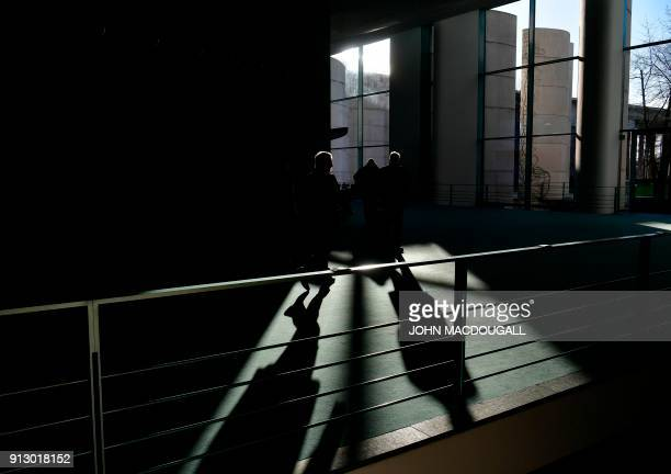 Participants walk to the meeting room where the German Chancellor hosts a meeting with regional state leaders as part of regular consultations on...