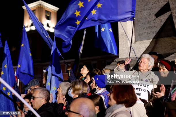 Participants wave EU flags as they take part in a pro-EU demonstration following a ruling of the Constitutional Court against the primacy of EU law...
