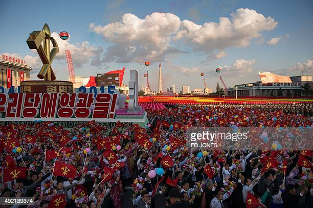 Participants wave flags and flowers as they pass through Kim IlSung square during a mass military parade in Pyongyang on October 10 2015 North Korea...