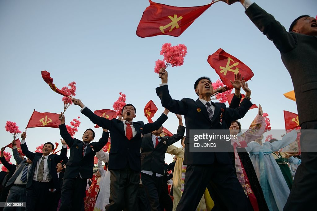 Participants wave flags and flowers as they pass through Kim Il-Sung square during a mass military parade in Pyongyang on October 10, 2015. North Korea was marking the 70th anniversary of its ruling Workers' Party. AFP PHOTO / Ed Jones