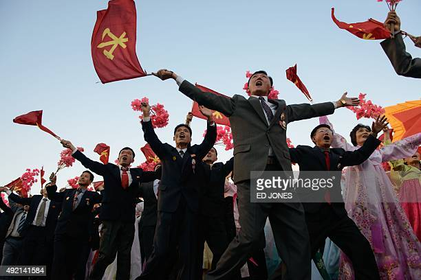 Participants wave flowers towards North Korean leader Kim JongUn as they pass through Kim IlSung square during a mass military parade in Pyongyang on...